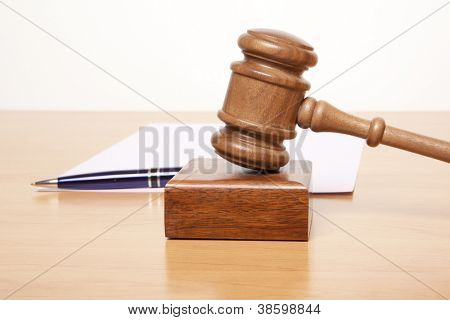 Gavel, a pen and a paper on the table