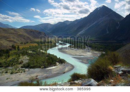 Turquoise River, Mountains And Skies.