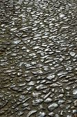 stock photo of pavestone  - The medieval cobblestone road is made of pebbles and shingles - JPG