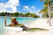 stock photo of french polynesia  - Polynesian wedding boat with chair at exotic beach - JPG