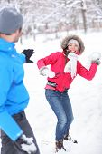 stock photo of snowball-fight  - Young couple playing in the snow in snowball fight with a vivacious smiling Asian girl taking aim at her husband with a snowball - JPG
