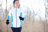 Running young Asian woman jogging in a winter fleece and gloves in open countryside with copyspace i