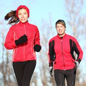 Healthy lifestyle winter running. Runner couple jogging in city park in warm winter sports clothing.