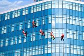 Five window cleaners on modern building