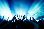 stock photo of audience  - cheering crowd in front of bright stage lights - JPG