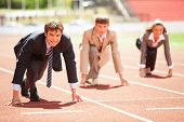 stock photo of competing  - Businessmen running on track racing at athletich stadium - JPG