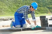 pic of banquette  - mason worker making sidewalk pavement with stone blocks - JPG
