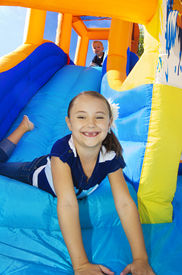stock photo of inflatable slide  - Kids playing on an inflatable slide bounce house - JPG