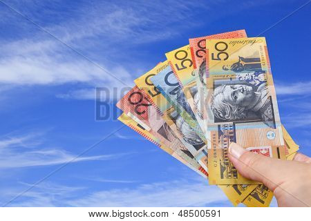 Handful of Australian money with blue sky background.