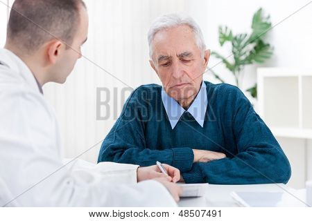Senior man at doctor'??s office, consulting with doctor