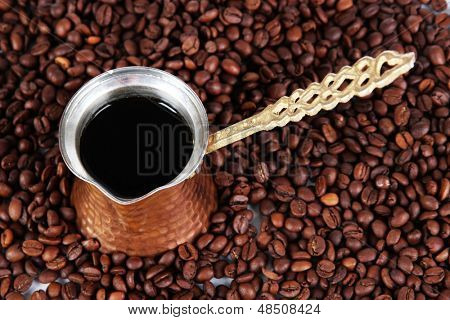 Coffee pot on coffee beans background