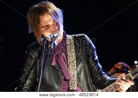 Young singer in leather jacket with closed eyes plays guitar and sings.