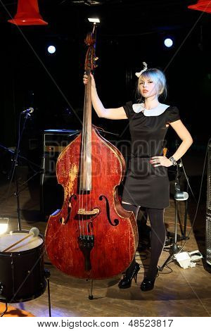 Young woman in black dress with wooden contrabass in night club.