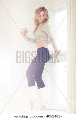 Beautiful sexy lady dancing by the window