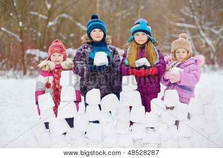 Children stand behind snow wall holding snow blocks, winter, park