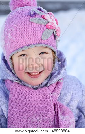 Little girl in pink scarf and hat smiles outdoor at winter day.