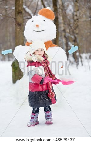 Little girl with red plastic shovel stands against big snowman