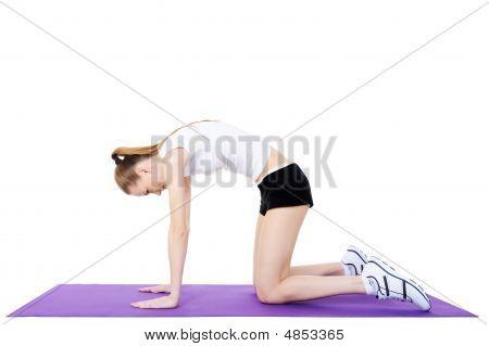 Gimnasia de joven en la alfombra de la gimnasia