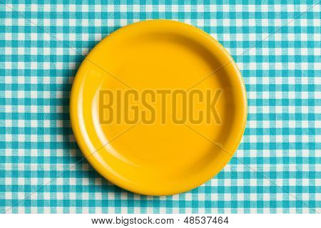 the empty plate on checkered tablecloth