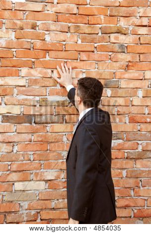 Businessman By Brick Wall