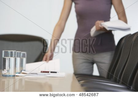 Midsection of a female office worker arranging documents on conference table