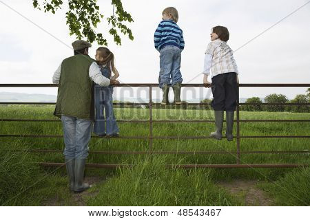 Full length rear view of father with three children looking at lush landscape by fence