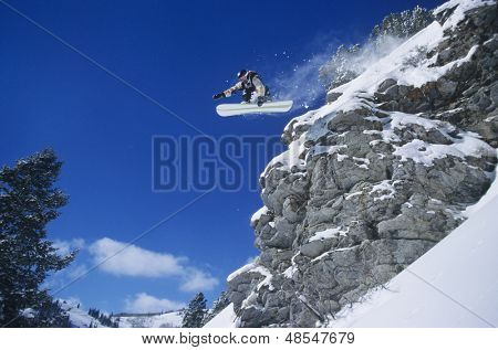 Low angle view of a person on snowboard jumping midair over cliff