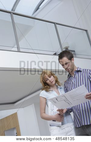 Low angle view of a young couple observing plan in new home