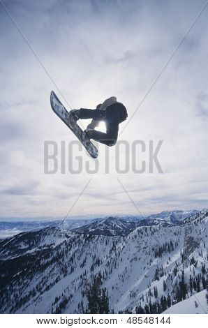 View of a person on snowboard jumping midair over snowed mountains