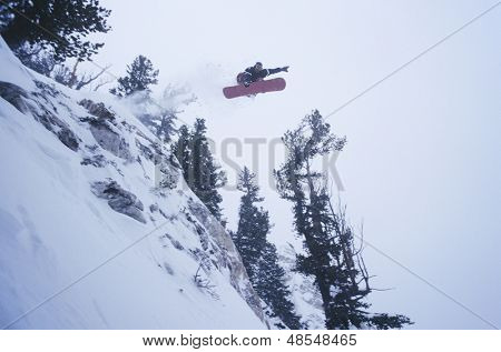 Low angle view of a person on snowboard jumping midair over snowed landscape