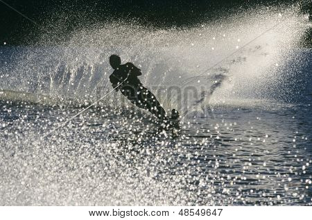 Full length of a silhouette male water skier in action