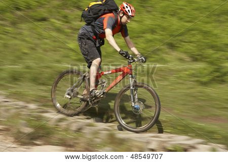 Side view of a male cyclist on countryside track