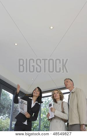 Female real estate agent and couple observing new property