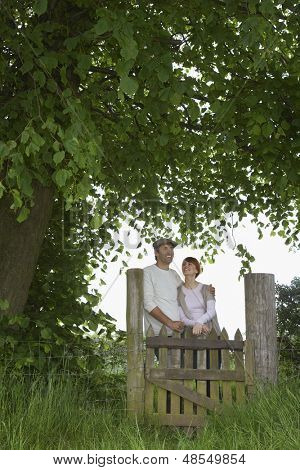 Thoughtful couple standing across field gate under the tree