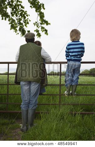 Full length rear view of father with two children looking at lush landscape by fence