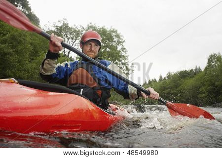 Low angle view of a young man kayaking in river