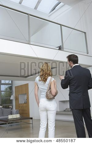 Rear view of a male real estate agent showing woman new home