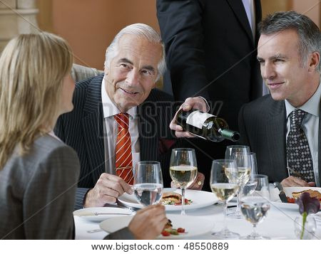 Three businesspeople talking at restaurant table as waiter serves wine