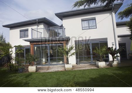 Exterior shot of a new house with balcony and lawn
