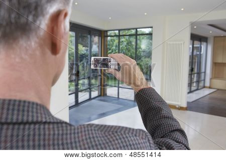 Closeup rear view of a male real estate agent photographing new property