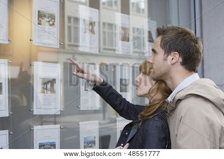 Side view of a young couple looking at window display at real estate office