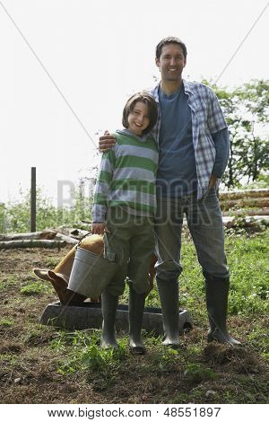 Full length portrait of a man and boy with pig in the sty