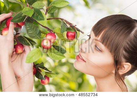 eco, bio and organic concept - beautiful woman with apple twig