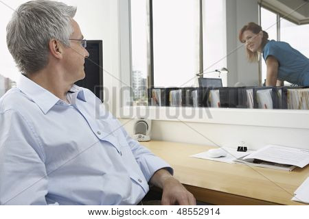 Middle aged male executive smiling at female colleague in office