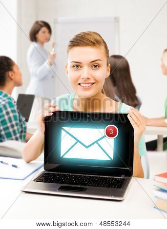 education, communication and internet concept - girl holding laptop with email sign at school