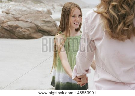 Happy preteen girl looking at mother while playing ring around the rosy on beach