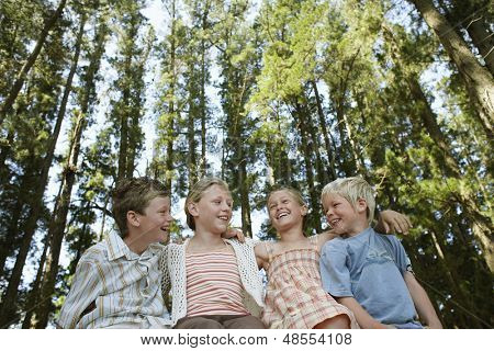 Low angle view of happy young boys and girls sitting arm around in forest
