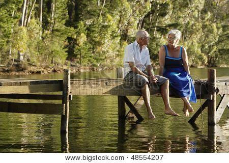 Full length of happy senior couple sitting on pier at lake