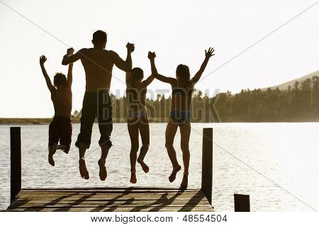 Rear view of father with children holding hands while jumping off a jetty
