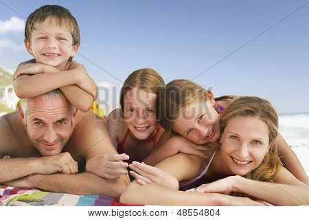 Portrait of Caucasian family lying together on blanket at beach against blue sky